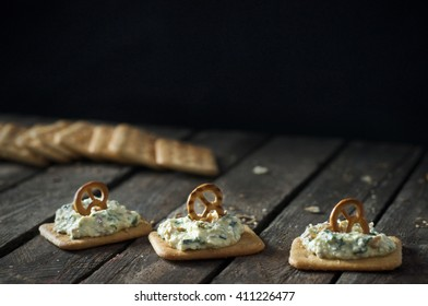 Finger food - crackers with cheese and sesame grain, topped with pretzel. Wooden table, dark black background. Place for text