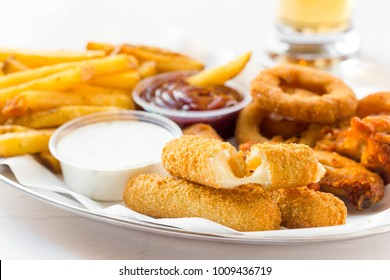 Finger food plate with fresh mozzarella sticks, onion rings, french fries and dip on white table.