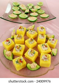 Finger food of tuna filled polentas and cucumber rounds ready to serve.