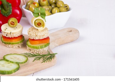 finger foods: bread, peppers, cucumber cheese and olives on white wooden table