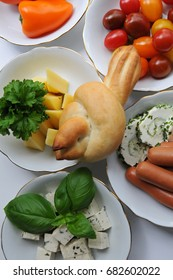 Finger foods for dementia patients - bread in a shape of a bird, small pepper, cherry tomato, cheese, parsley, frankfurter sausages, tofu with greens,fresh  basil leaves, bread spreads with chives