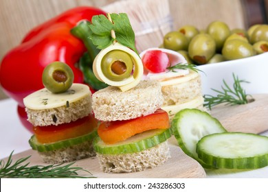 finger foods made of bread, peppers, cucumber cheese and olives on wooden table