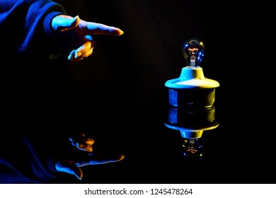 A finger and hand pointing to a dimly lit light bulb on a black background.