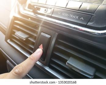 Finger hitting car emergency light botton, man pressing red triangle car hazard warning button,finger hitting car emergency light botton with sunlight.