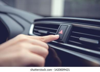 Finger hitting emergency light stop botton in the car , man pressing red triangle car hazard warning button.
