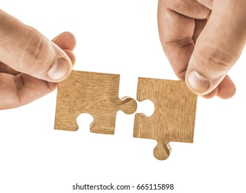 Finger holding two pieces of brown wooden puzzle. Isolated on white background. Slightly de-focused and close-up shot. empty Copy space. hand hold couple of piece on jigsaw