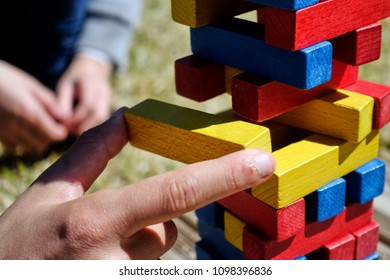 Kid's finger holding yellow wooden brick of balancing tower while playing it outdoors in sunlight.