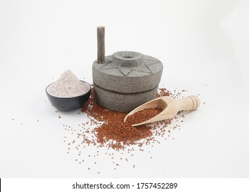 finger millet, ragi or nachani flour with seeds on traditional stone flour mill