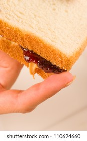 Finger next to dripping peanut butter and jam sandwich