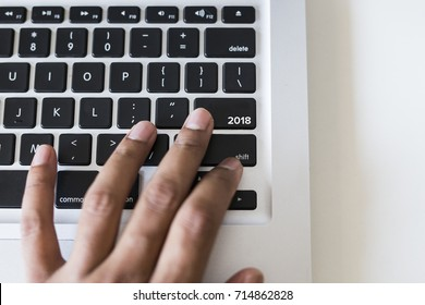 Finger on keyboard button with 2018 word