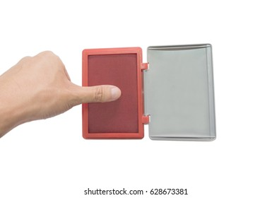 Finger on red ink stamp pad in front of a white background