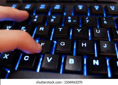 Finger over backlighted keyboard pressing the F character. Popular internet concept that stands for paying respects to someone.