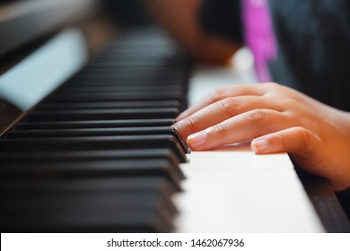 Children's finger playing on an acoustic piano. Close up. Selective focus