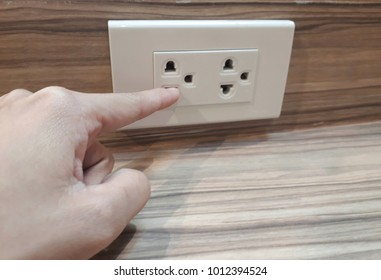 Finger plugging in electrical outlet on wood background or wood table , concept of do not uses finger plugging in electrical for safety.