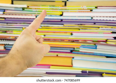 A finger pointing at the books.