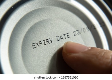 Finger pointing at the expiry date on canned food