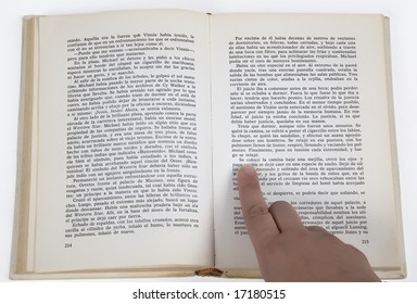 a finger pointing at the text of a book