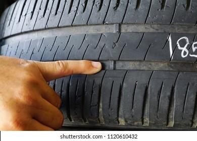 Finger, die auf die Reifenabzuganzeige zeigen / Reifungsprüfung und Austausch des Sicherheitskonzepts