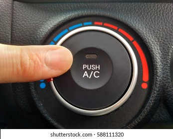 Finger presses the button of the air conditioner in the car