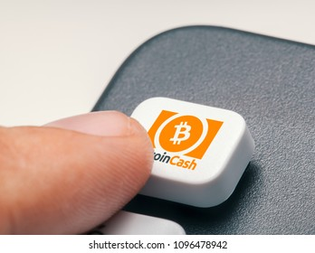 finger pressing computer key with bitcoin cash logo. crypto mining trading concept