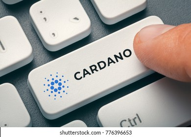 finger pressing computer key with cardano coin logo. cryptocurrency concept