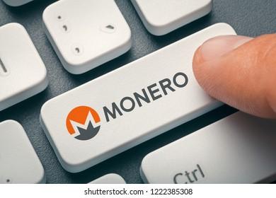 finger pressing computer key with monero coin logo. crypto mining concept