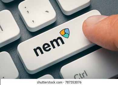 finger pressing computer key with nem coin logo. crypto mining concept