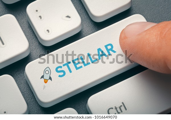 finger pressing computer key with stellar logo. cryptocurrency trading concept