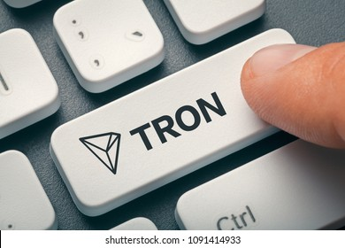 finger pressing computer key with tron coin logo. cryptocurrency trading concept