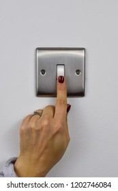 finger pressing a light switch on