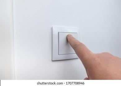 Finger pressing light switch to turn off light. Modern white light switch on white wall.
