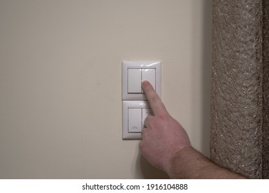 Finger pressing light switch to turn off the light. Modern white light switch on white wall