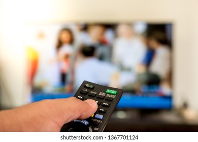 The finger is pressing on the black remote control button. TV is blurred background