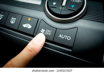 Finger pressing on Power button on off switch of a Car air conditioning and heating system To turn on the Fan of the A/C inside the Car