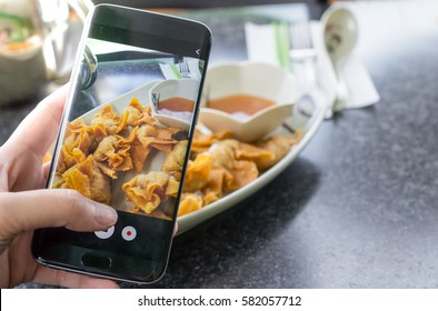 Finger pressing on smartphone for photograph chinese food in restaurant, for food ad or website promote