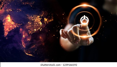 Finger pressing power button energy on earth at night background. Earth day. Environment and conservation. Energy saving concept.