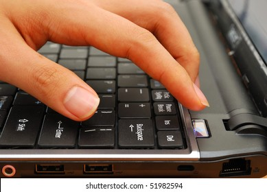 Finger pressing power button on laptop keyboard. For concepts such as electronics and technology, and office and business.