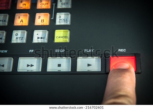 A finger pressing the record button on a digital recorder.