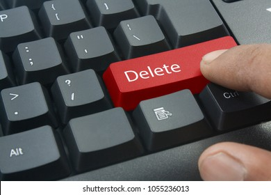 finger pressing red delete keyboard button