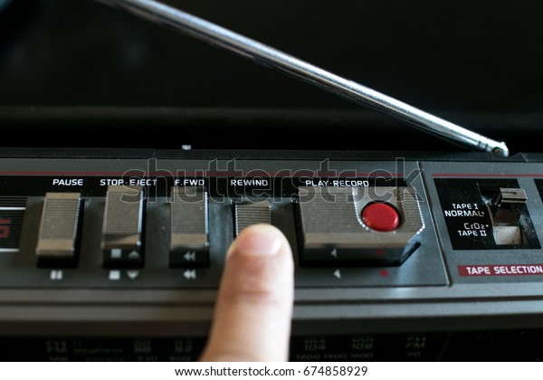 Finger pressing the Rewind button on an old stereo 80's