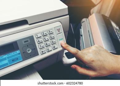 Finger pressing start button of fax machine , office equipment