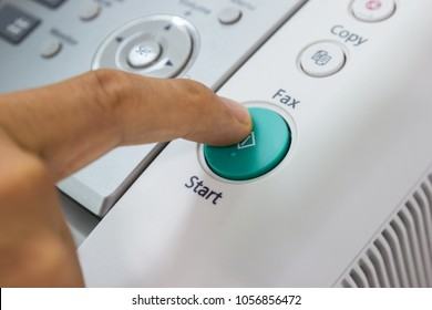 Finger pressing start button on the fax, business concept.
