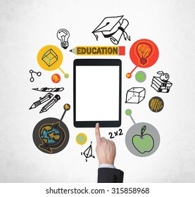 A finger is pushing the button on the tablet with blank screen. Educational icons are drawn around the tablet. A concept of education and technology.