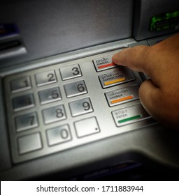 A finger pushing on a cancel key on an ATM machine keypad.