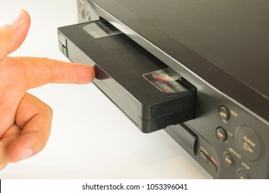 finger pushing a video cassette into the inside of a VCR for viewing recordings on a white background.