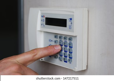 Finger setting security alarm, pressing keys on keypad