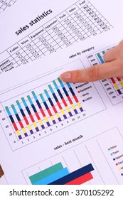 Finger showing financial chart, business concept, analysis of sales plan, business report, business work station with paperwork