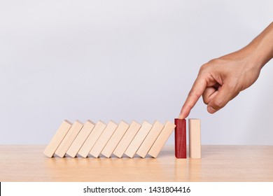 Finger stopping the domino on wooden table. Business strategy