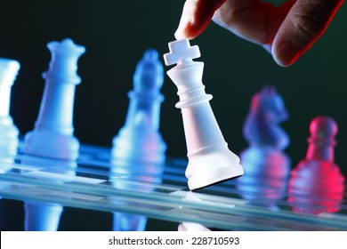 Finger tilting a chess piece on Chess Board Photo of a Finger tilting a chess piece on Chess Board