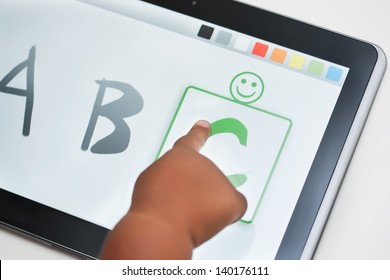 The finger of a toddler selecting the correct letter on a touchscreen tablet with learning software.